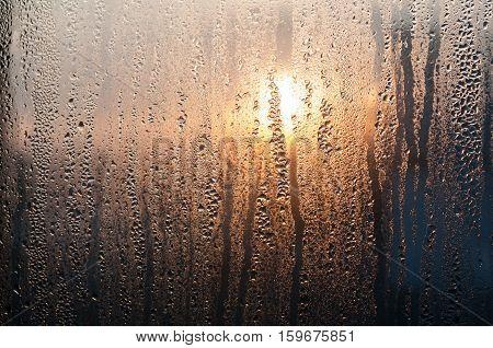 Water drops on glass window sunrise background