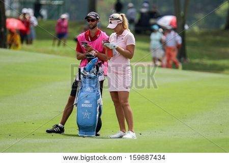 KUALA LUMPUR, MALAYSIA - OCTOBER 29, 2016: Anna Nordqvist of Sweden checks with her caddie at the fairway of the TPC Golf Course at the 2016 Sime Darby LPGA Malaysia golf tournament.