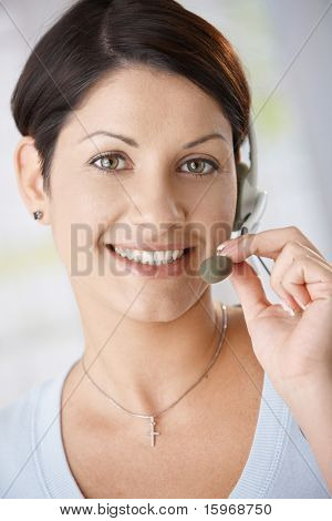 Closeup portrait of attractive woman talking on headset, holding on to microphone.?