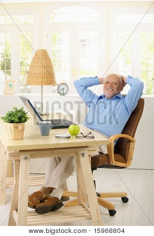 Portrait of cheerful old man in his study sitting relaxed at desk with hands on nape, looking at camera.?