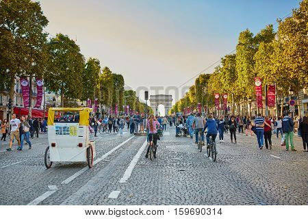 PARIS FRANCE - SEPTEMBER 27: The Champs-Elysees and the Arc de Triomphe on September 27 2015 in Paris France during Day without cars (Journee sans voitures) event