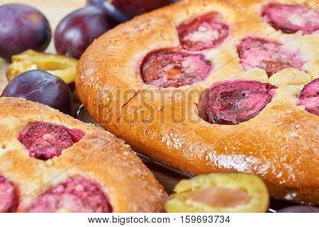 Home made plum buns on a wooden table