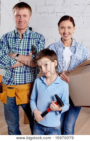 A young family looking at camera in new house