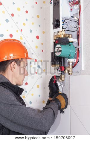 plumber installs household wall electric heating boiler