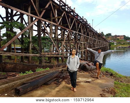 KANCHANABURI THAILAND - NOVEMBER 25: unidentified woman taking a photo at the old wooden Mon Bridge in Sangkhla Buri in the morning on November 25 2016 in Kanchanaburi Thailand