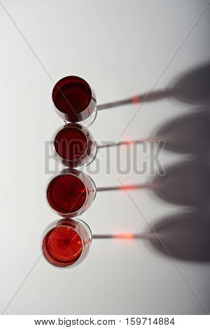 Line of glasses with red wine and shadows view from top