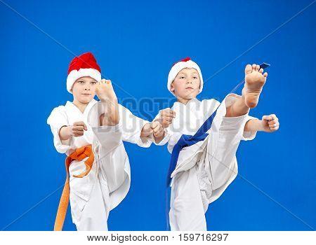 Children in caps Santa Claus are training kick leg