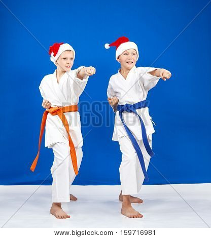 Two boys in caps of Santa Claus hit a punch arm in the rack of karate