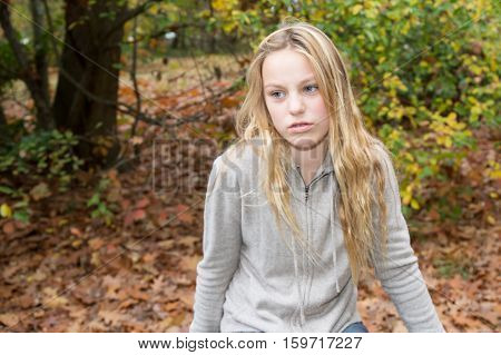A blond girl sadness in autumn park