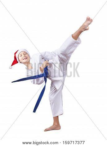 Sportsman in a cap of Santa Claus hits a kick leg