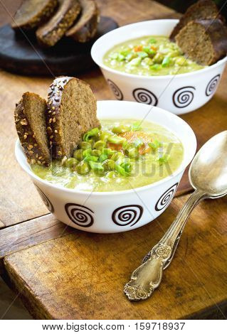 Vegetarian cream soup with bread toasts on a rustic wooden table, ready-to-eat