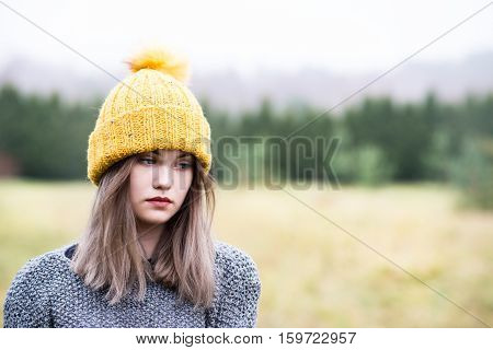 Thoughtful Young Woman In Woolen Yellow Cap