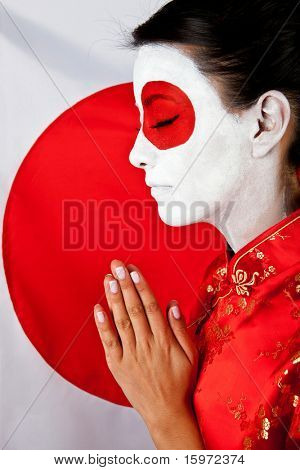 Woman making a prayer for Japan with the flag painted on her face