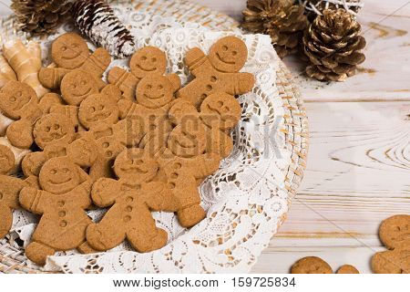 Christmas smiling gingerbread men men and women on white handmade lace with Christmas decoration