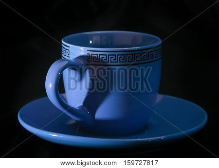 Cup and shadow on her in the form of a heart. The blue cup on a black background the handle casts a shadow in the form of heart