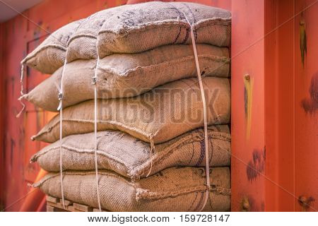 Jute sacks stacked in a warehouse - Cropped image with a pile of burlap bags full of goods stacked on a pallet in a storage and ready for shipment.