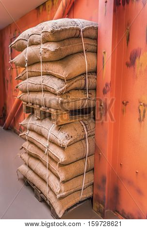 Pallets of merchandise bags stacked in storage - Industrial image of two pallets with goods in burlap sacks piled upon each other and stacked in a storage prepared for shipping.