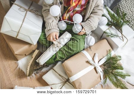 A little boy in a pile of Christmas presents