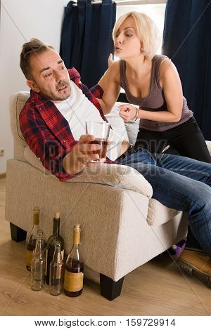 Couple man and woman having conflict while spending free time at home atmosphere. Blond wife screaming at her husband drunker. Alcohol concept.