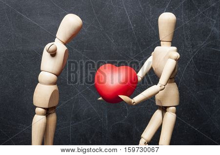 Concept protection of handicapped people. Wooden figure of healthy man gives another physically disabled figure without hands a big red heart as a symbol of love and care