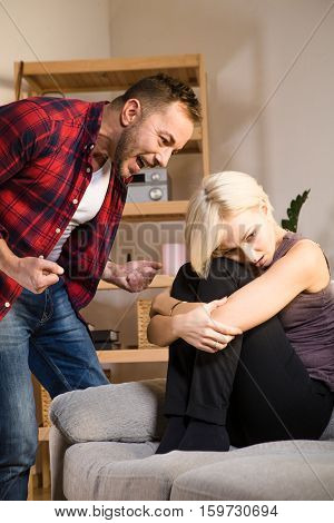 Couple man and woman having conflict and quarrel about family life at home. Angry man screaming and shouting at his wife while she is sitting on sofa or couch.