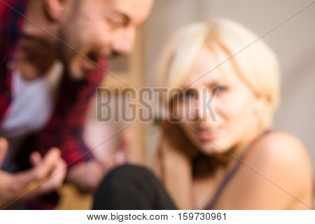 Toned picture of couple man and woman having conflict at home. Man screaming at his wife while she is sitting frightened on sofa or couch. Blured background.