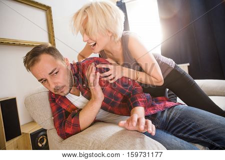 Angry blond woman shouting at her husband and asking about money. Couple man and woman having conflict and quarrel at home.