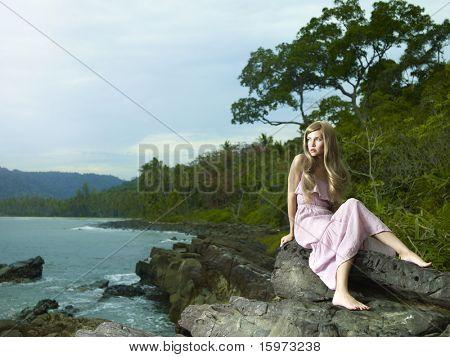 Fotos de una mujer hermosa en un vestido rosa en una costa rocosa