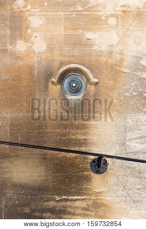 Old brass doorbell button on a beige stone wall and black painted metal stairs handle