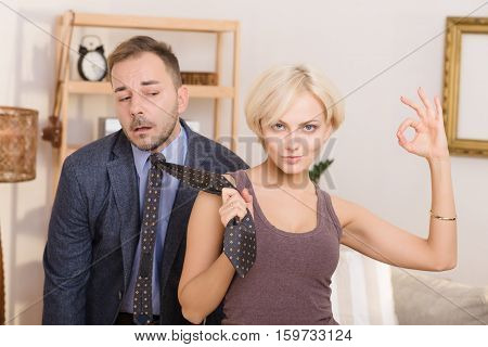Blond lady keeping tie in her hand and showing okay sign demonstrating that her husband under pressure. Family concept.