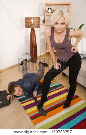 Family concept. Man under pressure of his wife. Man lying on floor while his wife standing on his tie. Family concept.