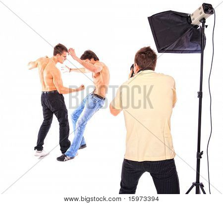 Two shirtless men fighting in studio white photographer is taking pictures over white background