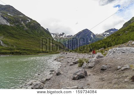 BRIKSDALSBRE, NORWAY - JULY 4, 2016: People are at the lake formed by the melting of the Briksdalsbreen glacier Norway.