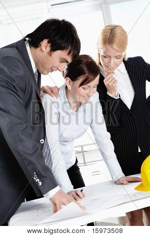Three businesspeople bending over construction plan