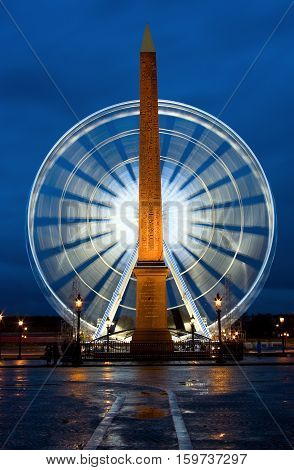 Night View Of The Egyptian Obelisk In Front Of Observation Wheel At Concorde Square, Paris, France