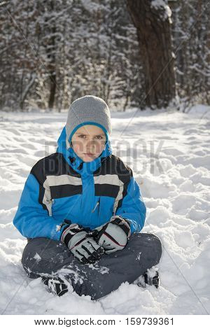 In winter a bright sunny day sad little boy sitting in the snow.