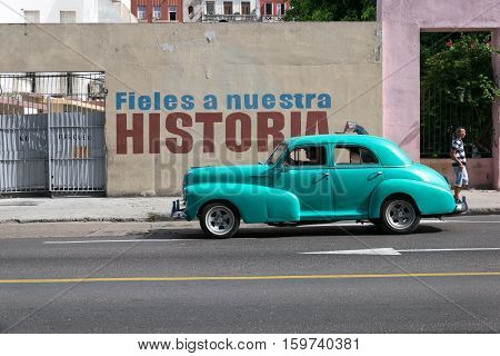 HAVANA, CUBA - JULY 1, 2015: Old american car passing by a patriotic stencil billboard