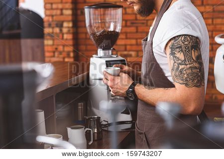 Confident barista is working in coffeehouse. He is standing and holding cup