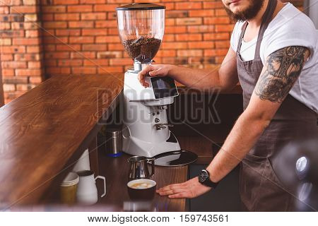 Professional male barista is working in coffeehouse