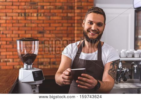 Drink this coffee. Joyful young barista is standing in coffeehouse and stretching cup to camera. He is smiling