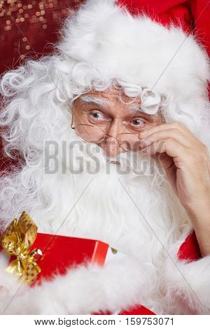 Santa claus offering a red gift against red background