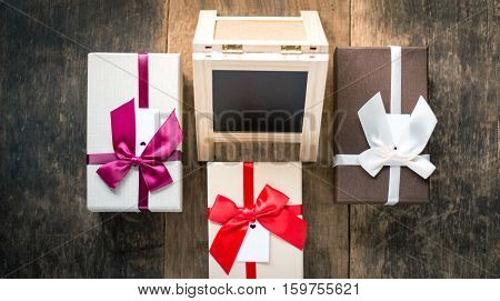 Three gift boxes and small backboard on wooden background