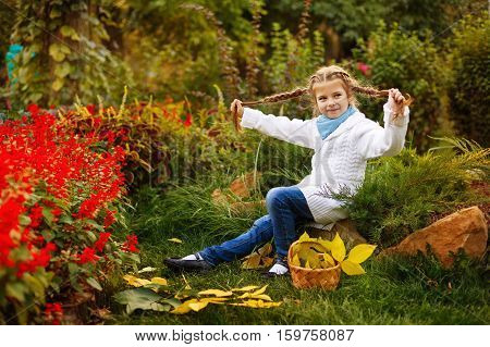 Cute little girl fooling around with her braids in the autumn park. Wicker basket standing beside her.