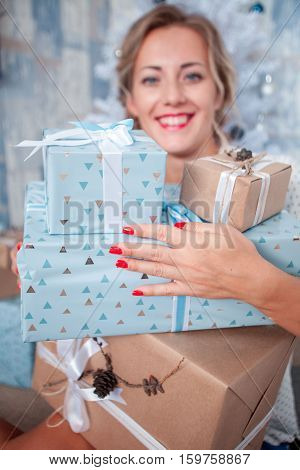 Merry Christmas. Attractive young woman holding gift boxes and smiling while standing on christmas light background and christmas tree.