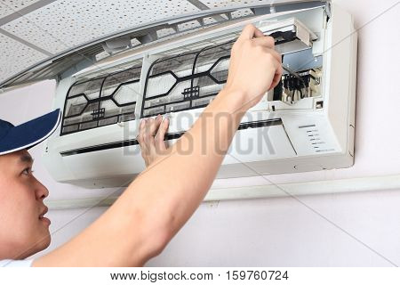 Young man adjusting air Conditioning System in bedroom.