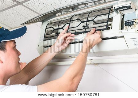 Young man Cleaning and washing maintenance dirty filter of air conditioner in bedroom.