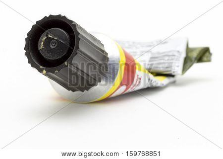 An empty tube of glue closeup on a white background.