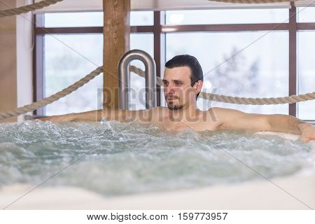 Confident handsome man relax in the tub with hydro massage in Spa salon