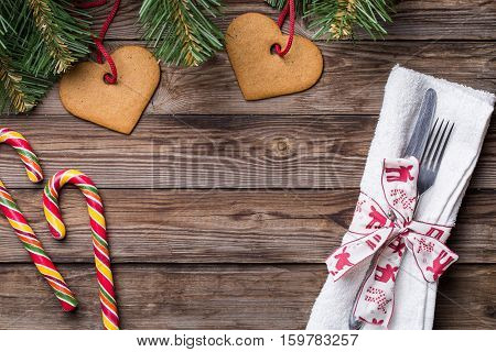 Christmas table place setting with fork and knife, decorated ribbon and bow, christmas pine branches, cookies and lollipop. Christmas holidays background.