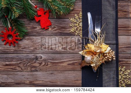 Christmas table place setting decorated black napkin with fork and knife, gold flower and snowflakes and christmas pine branches. Christmas holidays background.